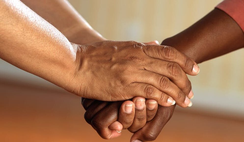 two people grasping each other's hands